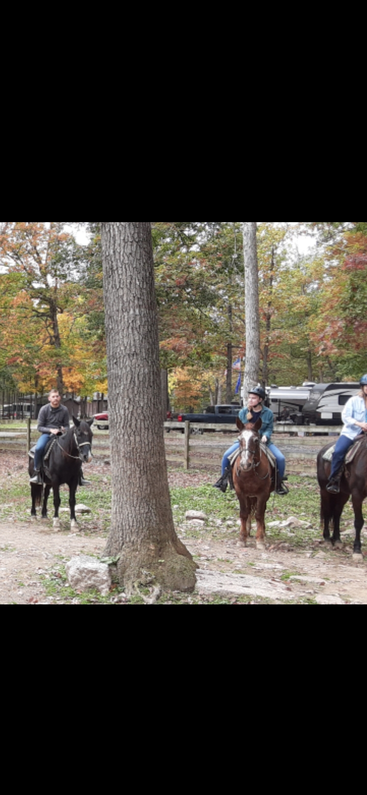 Guests horse back riding, with campground and cabins in back ground